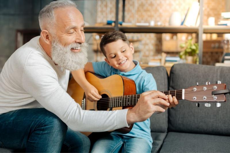 nonno insegna al nipotino a suonare la chitarra