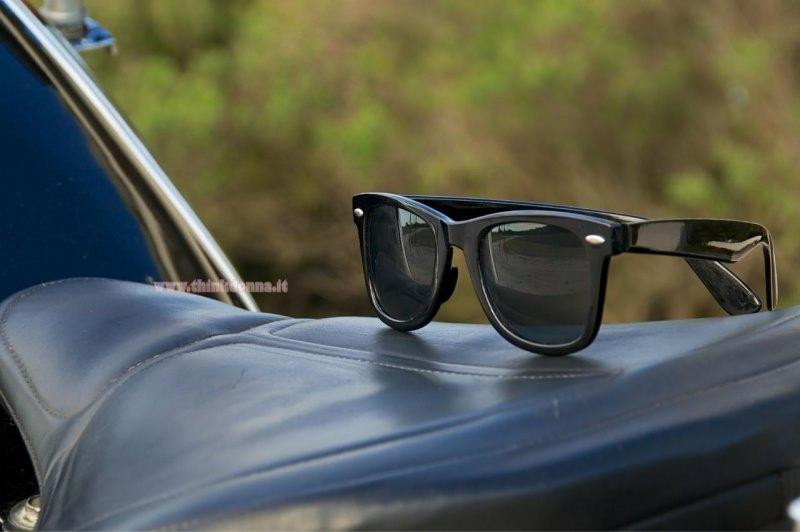 occhiali da sole Wayfarer nero sulla sella della moto