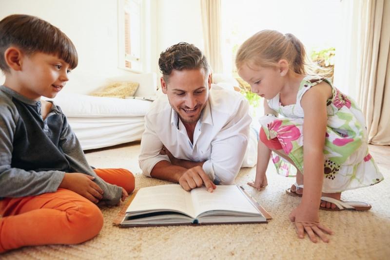 papà legge libro ai figli bambini