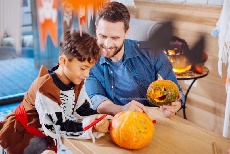 papà e figlio dipingono intagliano zucche halloween in casa