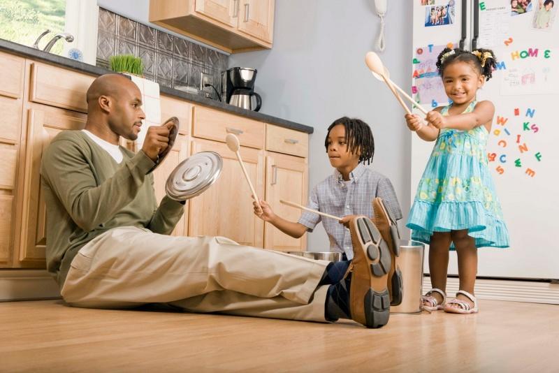 papà gioca con figli in cucina suonano coperchi pentole e mestoli