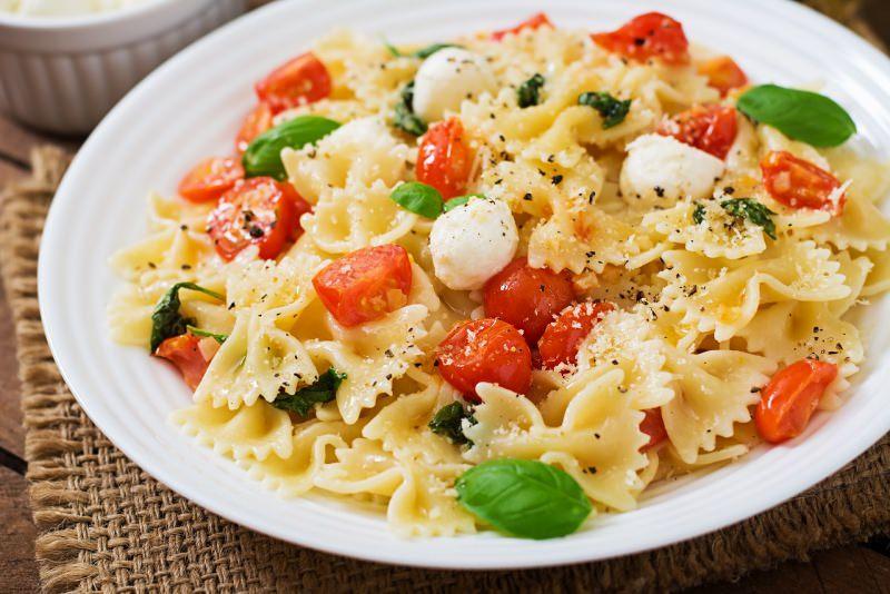 insalata di pasta farfalle fette di pomodoro rosso mozzarella fiordilatte foglie di basilico primo piatto pronto fresco