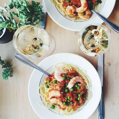 Come fare Linguine con gamberi, cipolla caramellata, pancetta e piselli primo piatto pronto tavola apparecchiata bicchieri vino bianco pianta grassa coltello