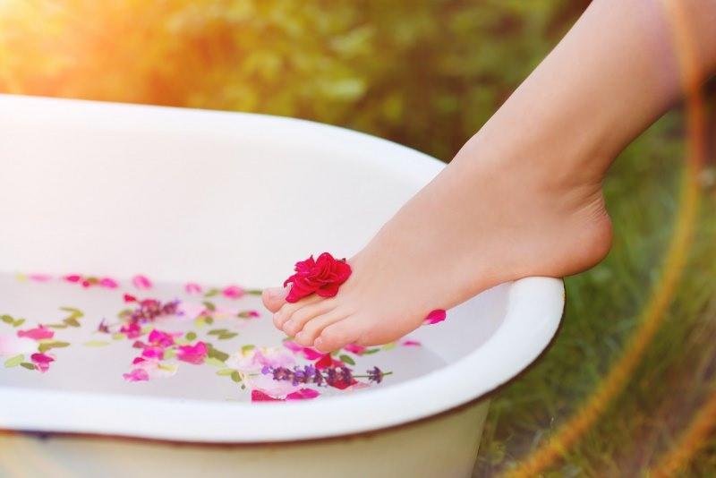 bellissimo piede donna pelle morbida talloni lisci vasca acqua petali rosa fiori