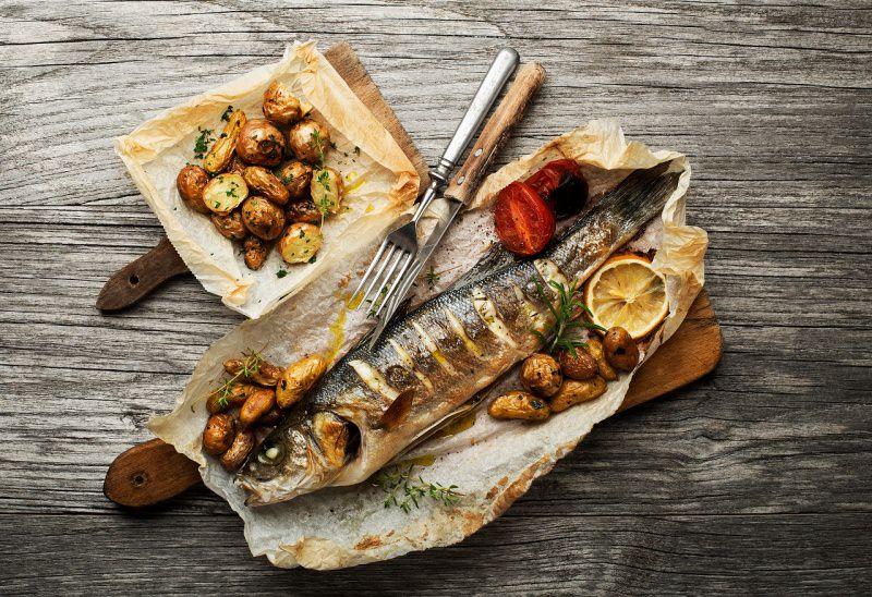 spigola al cartoccio patate pomodori posate coltello forchetta argento
