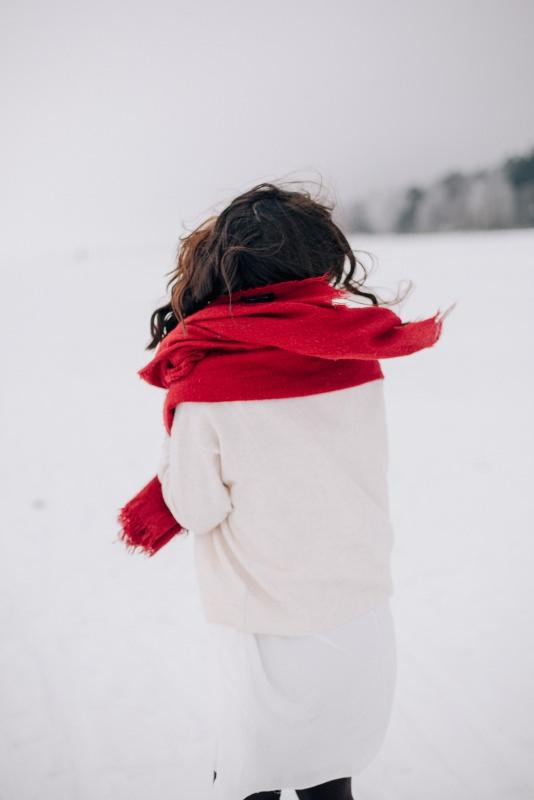 donna di spalle maglione bianco sciarpa rossa neve inverno