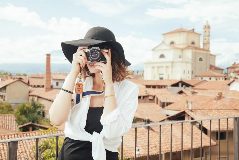 turismo donna cappello nero fotografa Viaggiare ad aprile, dove andare? Le migliori mete di viaggio per il Ponte di Pasqua.