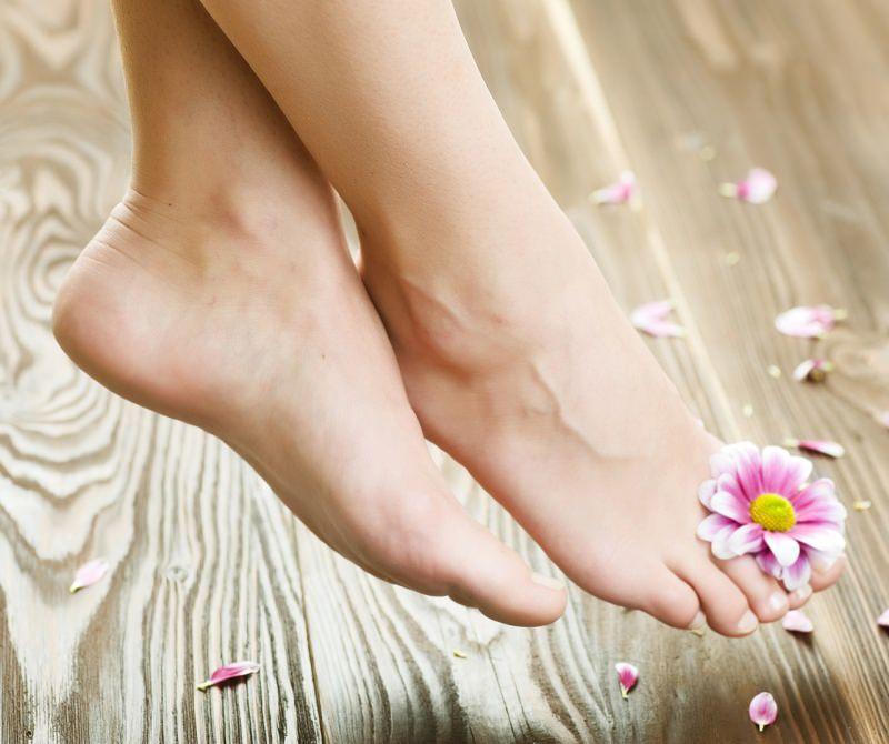 piedi bellissimi donna pelle liscia morbida talloni lisci fiore rosa tra le dita