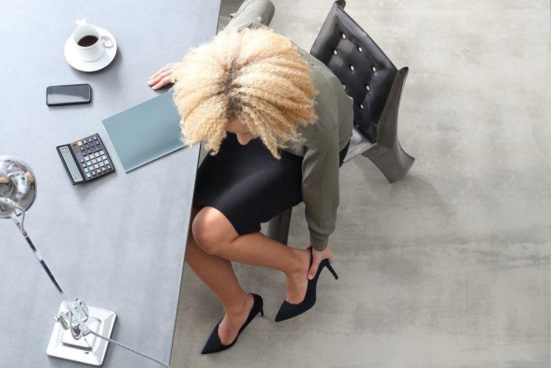 donna in ufficio scrivania tocca piedi doloranti tazzin caffè smartphone calcolatrice