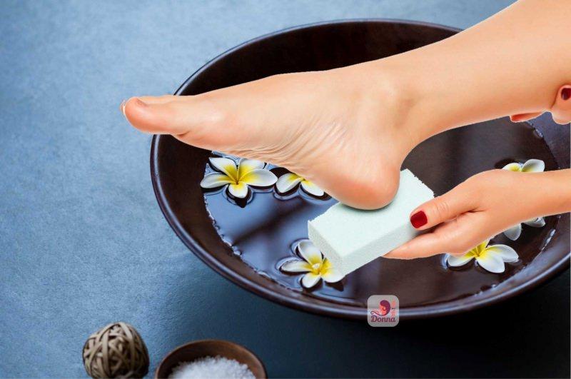 mano donna passa pietra pomice su tallone piedo ciotola pediluvio fiore tiarè