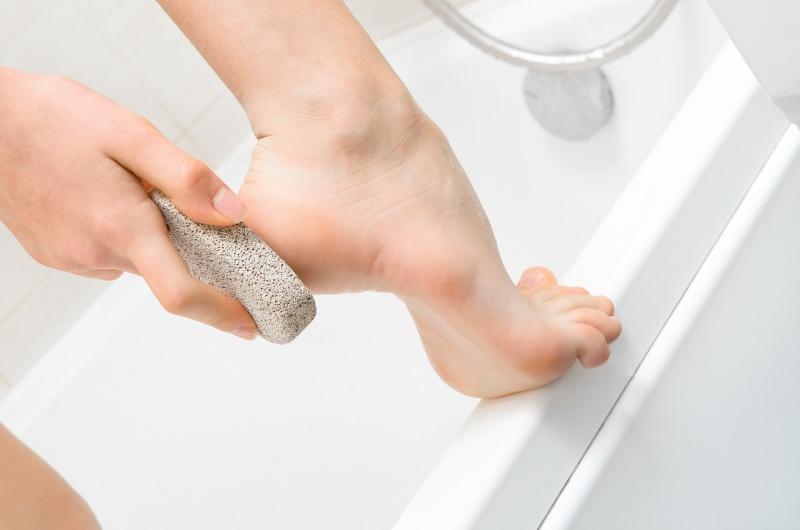 donna massaggia tallone piede pietra pomice