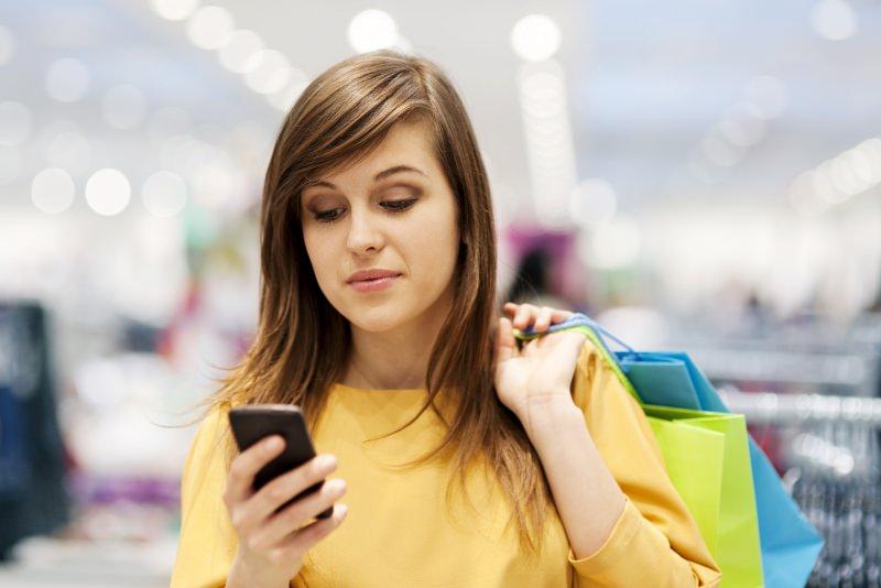 foto da playbuzz.com donna capelli lisci castano maglia gialla smartphone borse shopping Spedizioni economiche e anonimato: l'e-commerce a misura di donna