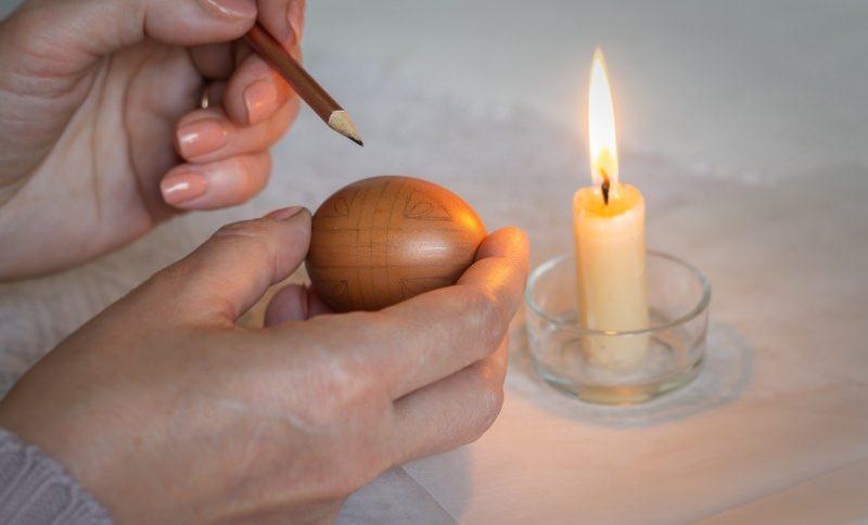 mano donna matita disegno su guscio uovo pasqua candela fiamma accesa