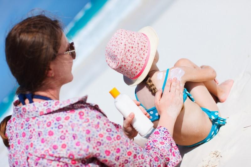 donna mamma mette protezione solare spalle figlia bambina cappello costume da bagno spiaggia sabbia mare estate