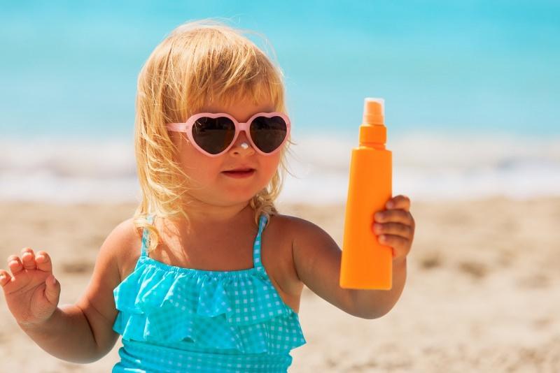bambina baby capelli biondi occhiali sole protezione solare flacone pray estate mare sole