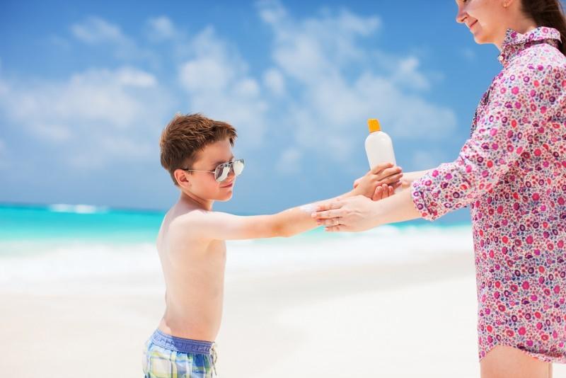 mamma mette protezione solare figlio bambino mare sole estate occhiali da sole spiaggia