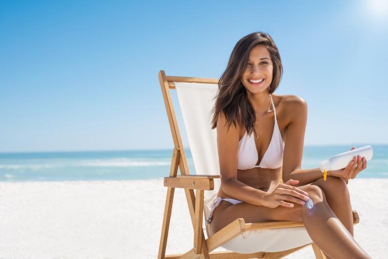 giovane bella donna in bikini bianco applica protezione solare sulla pelle sdraio estate mare spiaggia sole