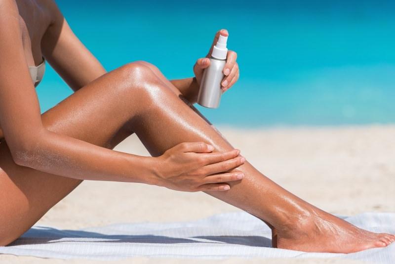 protezione solare spray su pelle abbronzata corpo donna costume da bagno due pezzi estate mare spiaggia