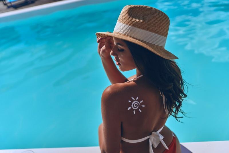 giovane e bella protezione solare donna crema solare a forma di sole sulla spalla cappello piscina estate bikini