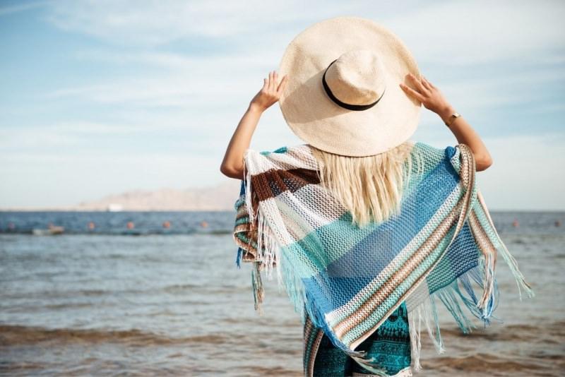 donna di spalle con cappello e poncho frange in riva al mare estate prova costume
