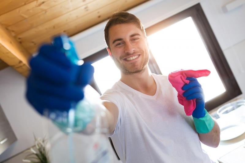 uomo sorriso pulisce vetri panno spruzzino pulizie