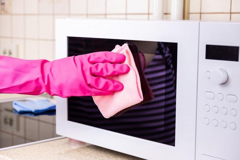 pulizia forno a microonde a mano con guanti di gomma rosa