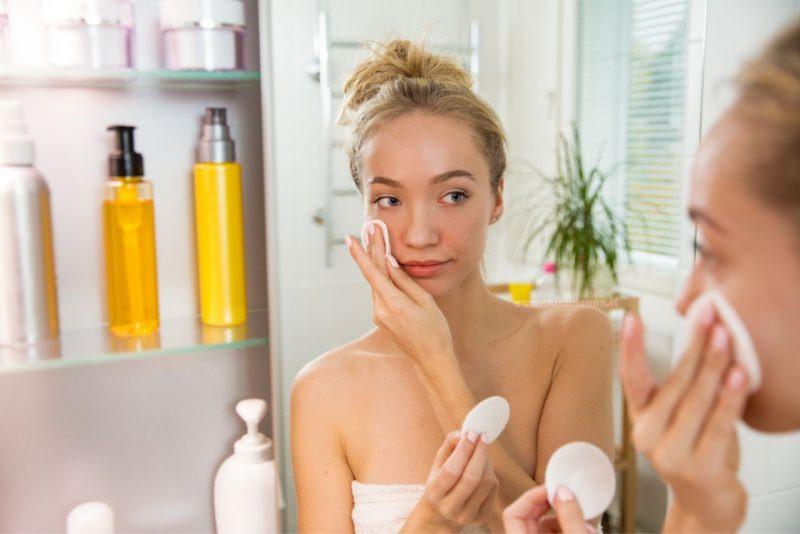 donna pulizia viso batuffoli di cotone davanti specchio bagno