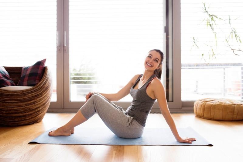 donna seduta su tappeto fitness sorriso casa