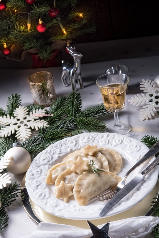 ravioli di pesce primo piatto di magro pronto tavola apparecchiata albero di natale luci renna argento tealight