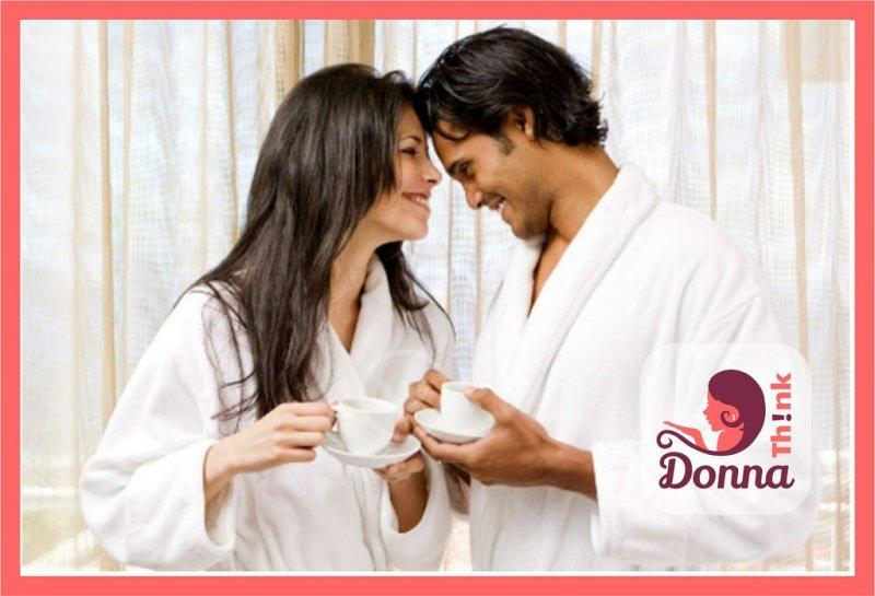 Regali San Valentino per lei e per lui originali, economici e fai da te amore in accappatoio coppia donna capelli lunghi castani sorriso denti uomo mattino tazzine caffè porcellana bianca piattino