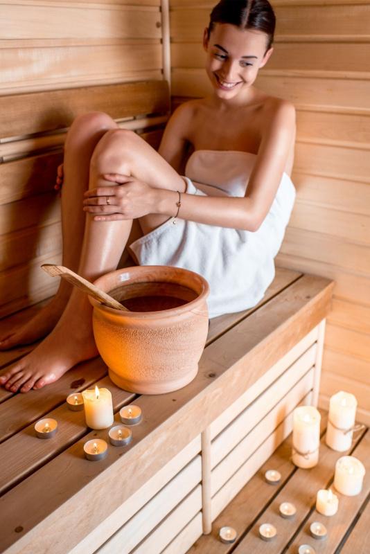 sauna finlandese legno relax donna sorridente sorriso vaso terracotta acqua candele fiamma accesa tealight
