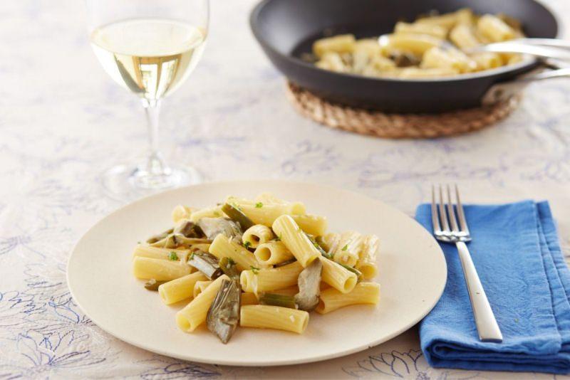 rigatoni saporiti ai carciofi piatto pronto tavola bicchiere calice vino bianco padella