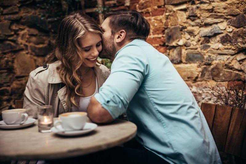 giovane coppia donna sorridente uomo sussurra orecchio