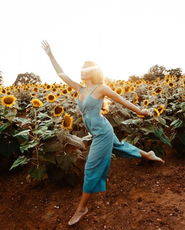 Salopette e jumpsuit: l'inconfondibile stile del pezzo unico campo girasoli donna capelli biondi sole