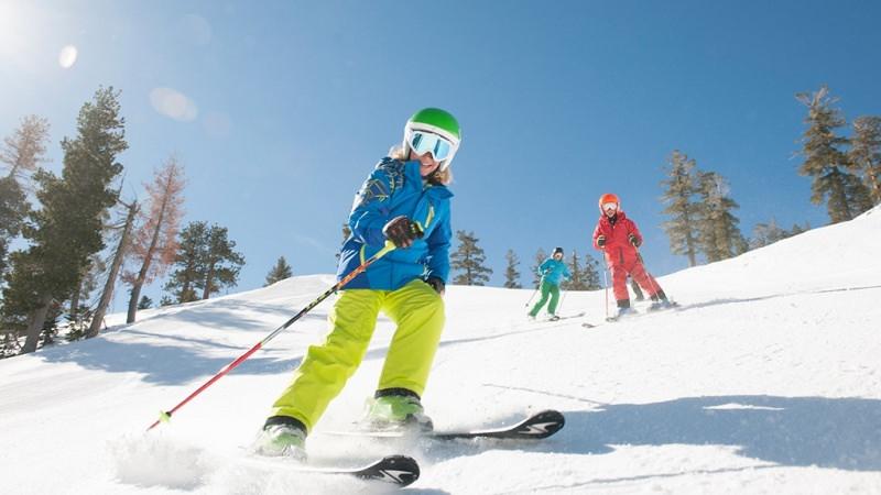 Cosa regalare per Natale a un ragazzo o ragazza? Idee regalo per adolescenti sciare neve bambina capelli biondi sci giubbotto azzurro pantalone giallo rosso alberi montagna