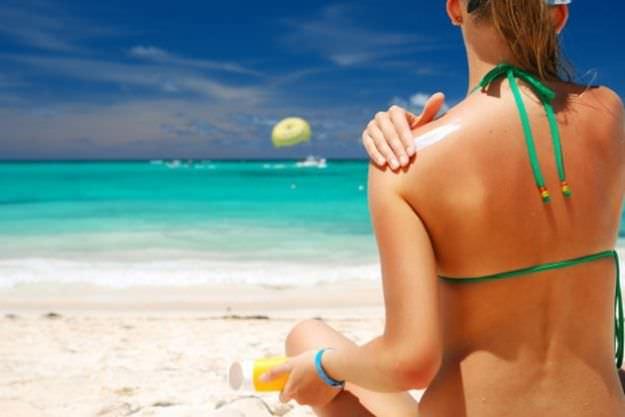 eritema solare estate mare spiaggia donna capelli lisci biondi coda cavallo ponytail bikini verde crema protezione solare braccaile azzurro
