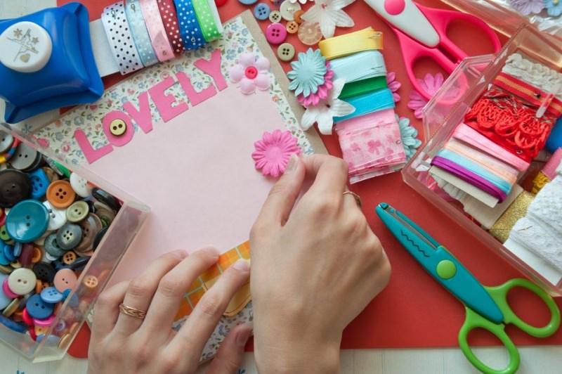 Scrapbooking, come conservare e presentare la tua storia personale in modo originale bottoni colorati fiori rosa celeste nastri pois nastro raso forbici mani donna anello oro