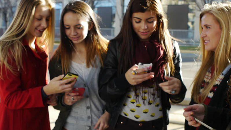 Tornare a scuola: ecco come affrontare lo stress da rientro vacanze i ricordi smartphone ragazze capelli lisci lunghi biondi giacca rossa maglietta bianca pull grigio giubbotto pelle nero capelli castani sorrisi