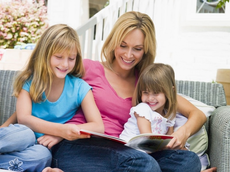 Tornare a scuola: ecco come affrontare lo stress da rientro leggere mamma donna capelli lisci biondi maglia rosa sorriso ora lettura figli bambinamaglietta azzurra jeans fiore bimba maglietta bianca ricami rosa divano
