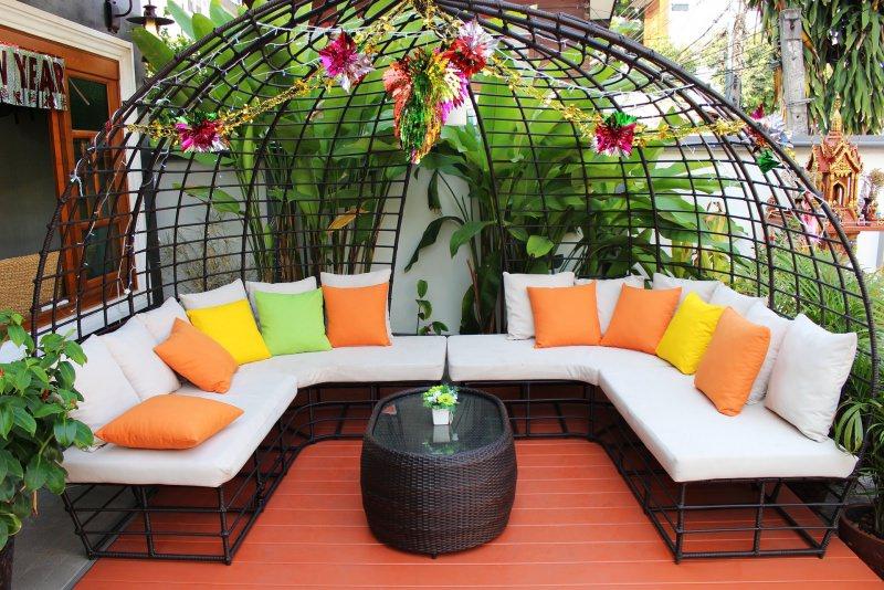Come creare uno spazio accogliente in giardino o terrazzo sedili bianchi cuscini colorati arancione giallo verde pianta tavolino vaso fiori addobbo