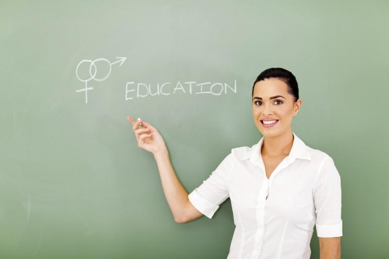 Perché abbiamo così paura di parlare di sesso? educazione sessuale lavagna simbolo genere femminile maschile donna capelli castano scuro legati sorriso denti bianchi occhi castani camicia bianca insegnante