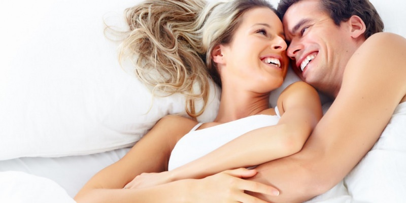Perché abbiamo così paura di parlare di sesso? intimità comunicazione partner moglie compagna donna capelli lunghi biondi sorriso uomo marito compagna capelli castani sorridere letto matrimoniale cuscini lenzuola bianche