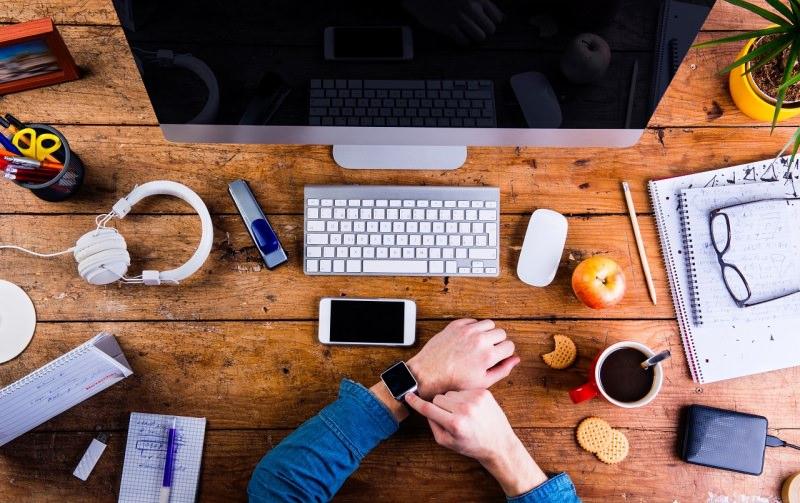 work station postazione lavoro smart working scrivania mano uomo orologio monitor cuffie tazzina caffè biscotti mela smartphone