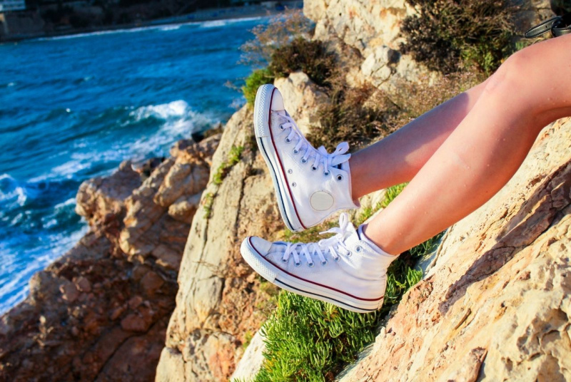 scarpe sneakers di tela bianche mare scogliera scoglio estate