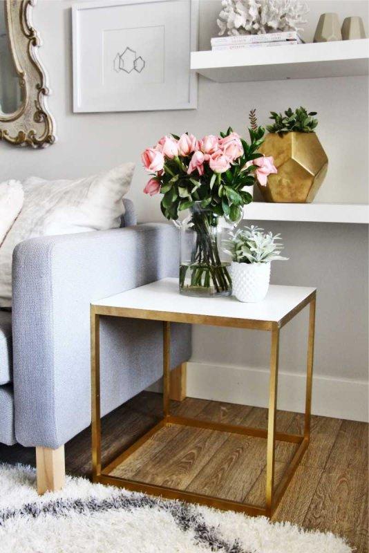 Arredamento trendy: cosa aspettarsi dal 2018? tavolino vaso ottone quadro bianco vaso vetro bouquet rose rosa vasetto bianco pianta grassa divano grigio mensola libri parquet tappeto