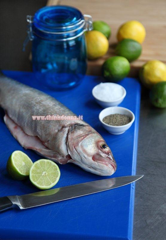 spigola fresca pulita tagliere blu limoni barattoli