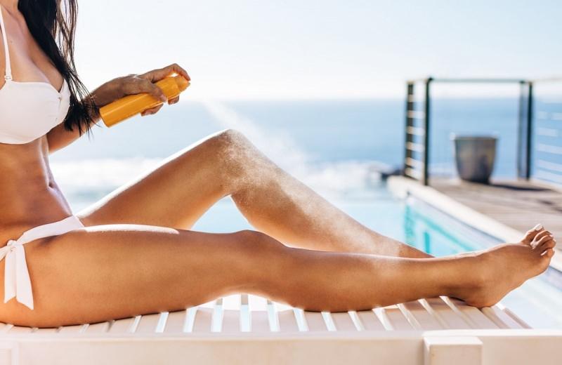 protezione solare donna bikini bianco spruzza spray solare su pelle abbronzatura mare estate