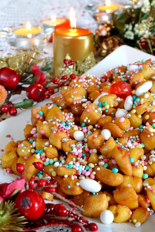 struffoli decorazione natalizia confetti candele fiamma accesa