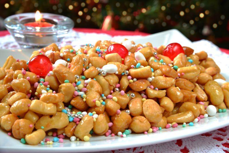 ecco come preparare gli struffoli cicerchiata vassoio frutta candita coriandolini zuccherini natale dolci candela fiamma accesa porta lumino vetro albero natale luci