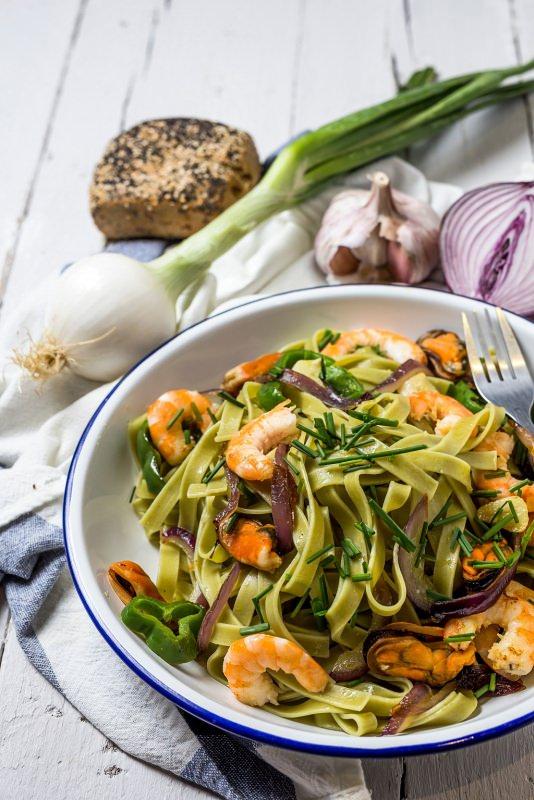 tagliatelle verdi con frutti di mare cozze gameri piatto pronto cipolla aglio